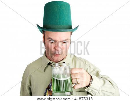 Drunk Irish-American man looks into his green beer on St. Patrick's Day.  Isolated on white.