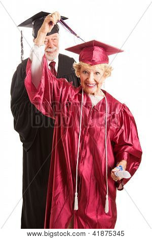 Ambitious senior woman moves the tassel on her mortar board to the other side at her graduation ceremony.  Isolated on white.