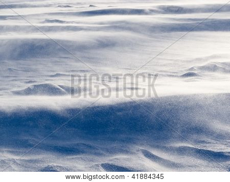 Wind drift snow flying over snow surface refief