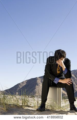 Full length of a depressed businessman sitting on briefcase in desert