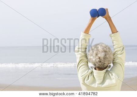 Rear view of an African American senior woman exercising with two dumbbells at beach