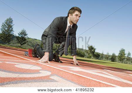 Vista de ângulo baixo de um empresário confiante em começar a posição de uma pista de corrida