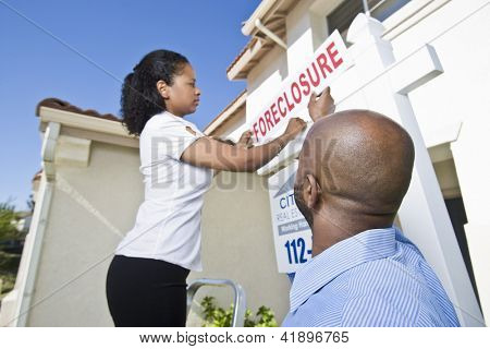 Low angle view of couple putting notice outside the house