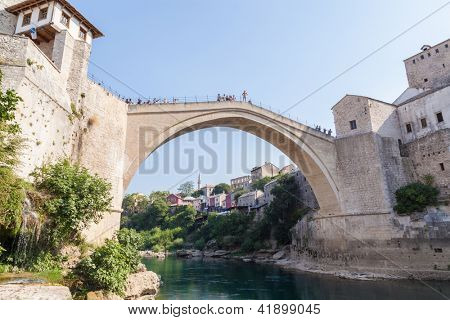 MOSTAR, BOSNIA - AUGUST 10: Man ready to jump from old bridge on August 10, 2012 in Mostar, Bosnia. It is a tradition for men to dive off the 21m bridge to impress visitors and earn some extra money.