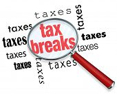 stock photo of irs  - A magnifying glass hovering over the word tax breaks - JPG