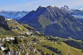 Green Alpine meadows adjoin to the first easy snow.  The magnificent Swiss Alps in an early autumn