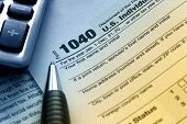 stock photo of irs  - US tax form 1040 with pen and calculator - JPG