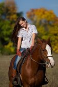 picture of straddling  - Beautiful girl  straddling a horse in garden - JPG