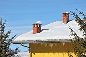 Two red brick chimneys and row of icicles on the roof covered by snow under blue winter sky in Piedm