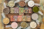 stock photo of flax seed  - superfoods word in letterpress wood type surrounded by plastic scoops of healthy seeds and powders  - JPG