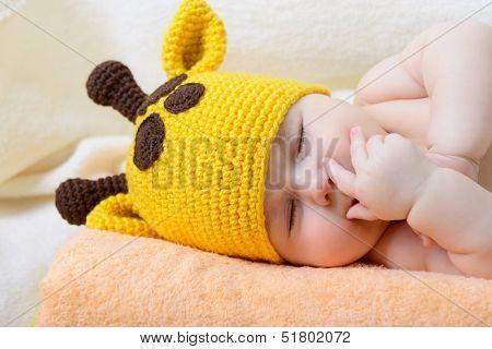 cute sleeping baby boy in funny hand made giraffe hat, beautiful kid dozing on plaid, studio shot