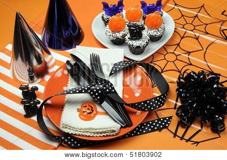 Happy Halloween Party Table With Orange Polka Dot Plates An Chocolate Cupcakes With Black Cat, Pumpk