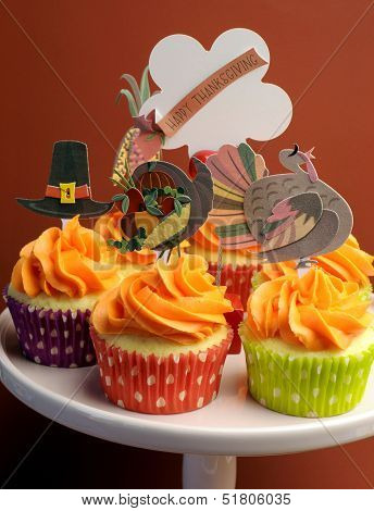Happy Thanksgiving Decorated Cupcakes With Turkey, Pilgrim Hat And Corn Toppers On Cake Stand Agains