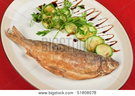 Fried peled fish with cucumbers and greens