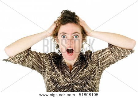 Horrified, appalled or amazed young woman with wide open staring eyes and an open mouth raising her hands to her hair in an emotional reaction, isolated on white