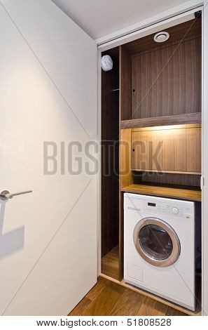 open door on a utility room with wooden shelving and washing machine