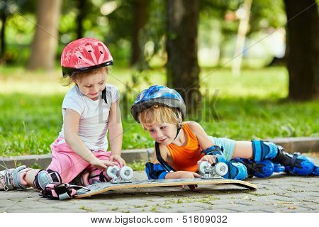 Little boy and girl in roller equipment sit on walkway in summer park and look upon upturned skateboard