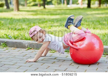 Little girl plays with red ball for jumping on  walkway in summer park, hands on ground, legs on ball