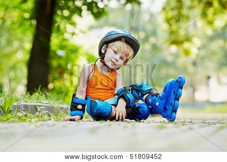 Little boy in protective equipment and rollers sits on walkway in park, leaning one hand on ground