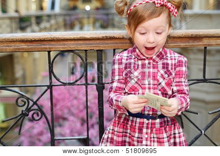 Little cute girl with papers stands near wrought railings and admires.