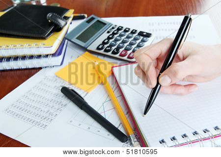 Woman hand with pen on worktable background
