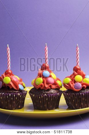 Bright Candy Covered Cupcake On Yellow Polka Dot Plate Against A Purple Background For Childrens Bir
