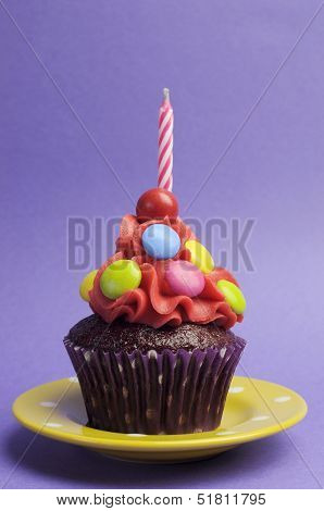 Bright Candy Covered Cupcake With Candle On Yellow Polka Dot Plate Against A Purple Background For C