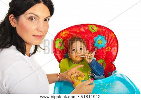 Mother Giving Food To Messy Baby