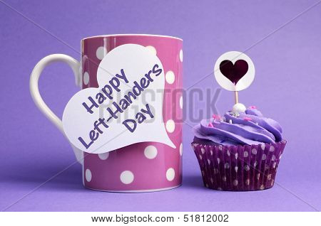Happy Left Handers Day Message Written On White Heart Shape Tag On Pink Polka Dot Mug With Purple Cu