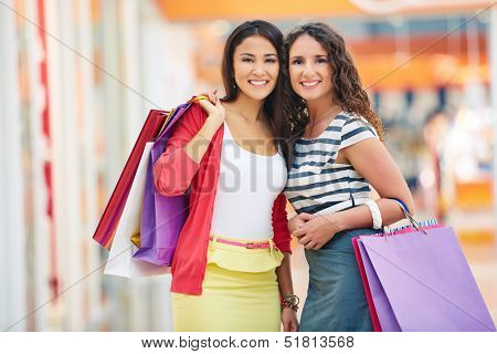 Gorgeous girlfriends with paperbags looking at camera in trade center