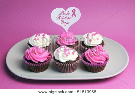 Pink Ribbon Day Message Across White Heart Toppers On Pink And White Decorated Red Velvet Cupcakes O