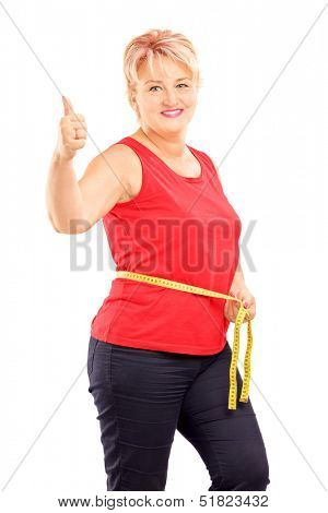 Happy mature woman measuring her waist after diet and giving thumb up, isolated on white background