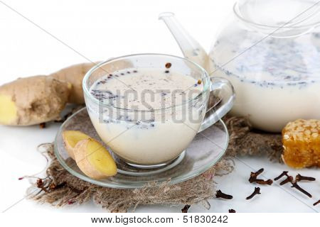 Teapot and cup of tea with milk and spices on sackcloth isolated on white