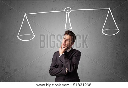 Young businessman taking a decision with scale above his head