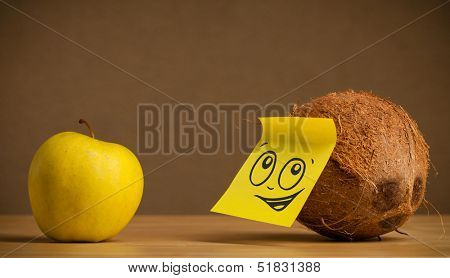 Coconut with sticky post-it note reacting to apple