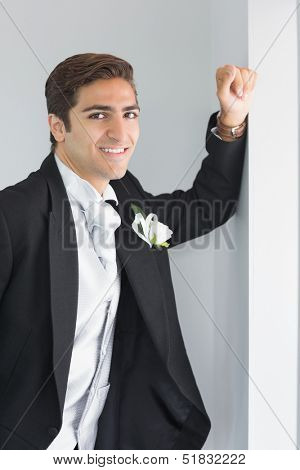 Cheerful young bridegroom leaning against wall smiling at camera