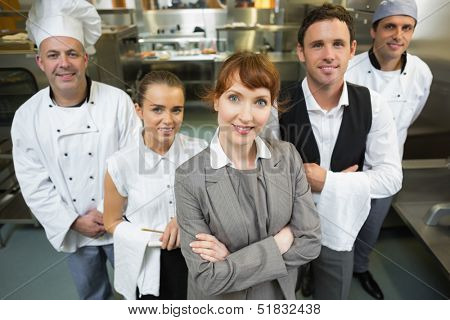 Cute female manager posing with the staff in a modern kitchen