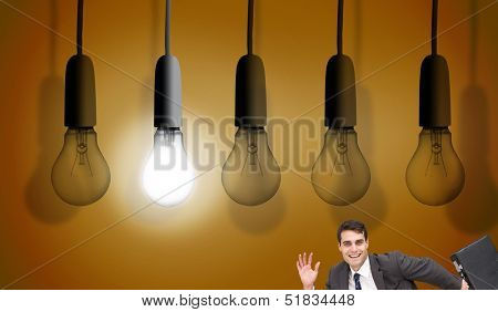 Composite image of happy businessman holding a briefcase and running under huge light bulbs on orange background