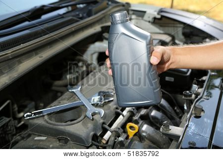 Auto mechanic hand holding motor oil