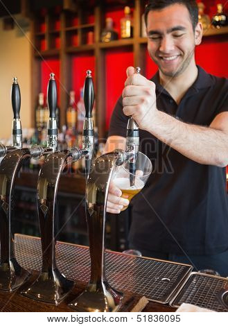 Handsome barkeeper pulling a pint of beer and smiling behind the bar