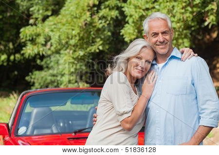Cheerful mature couple posing against their red cabriolet