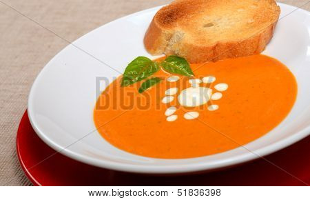 Delicious bowl of homemade tomato soup with grilled bread, basil and sour cream