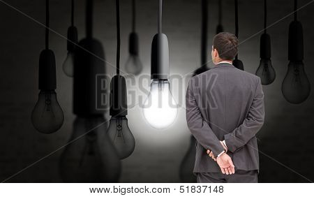 Composite image of businessman standing with hands behind back in dark room with glowing light bulb