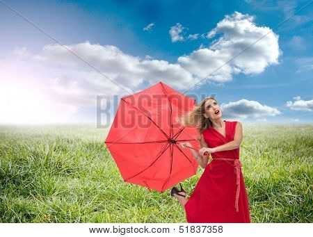 Composite image of beautiful woman wearing red dress holding umbrella standing on grass under sunny sky
