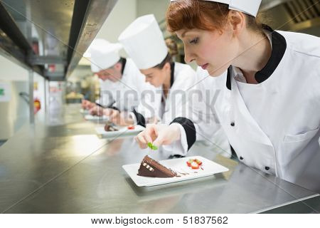 Chefs standing in a row garnishing dessert plates in the kitchen