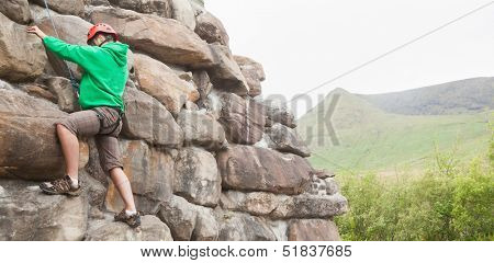 Determined man climbing a large rock face with mountains in the background