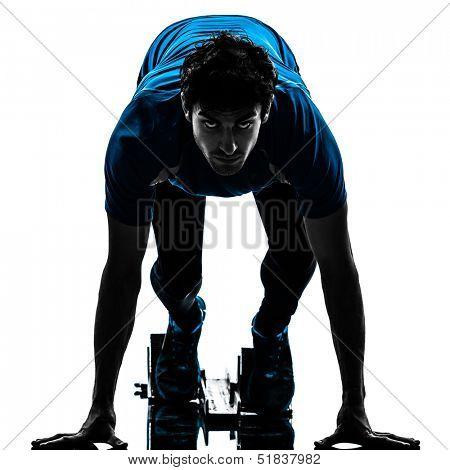 one caucasian man runner sprinter on starting blocks  in silhouette studio isolated on white background