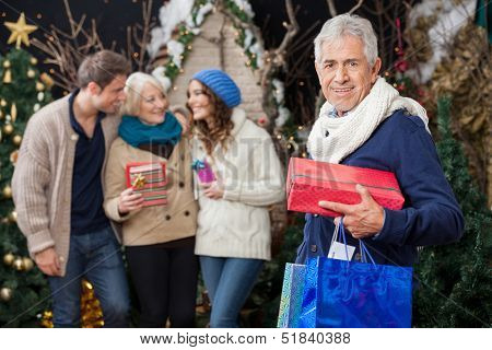 Portrait of happy senior man holding Christmas presents with family standing in background at store