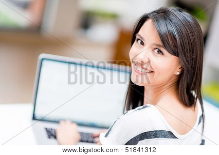 Woman working online on a laptop computer at home