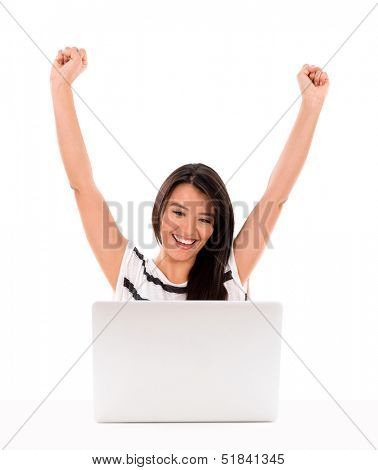 Happy woman winning something online with arms up - isolated over white